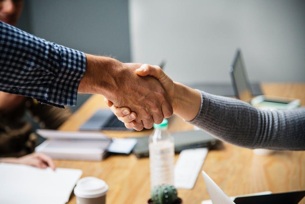handshake over a desk - trust in food business