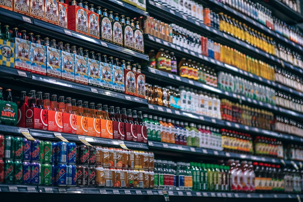 bottles and cans lined up on supermarket shelves